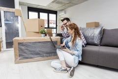 Couplez se reposer sur le sofa dans l'appartement avec l'ordinateur image stock