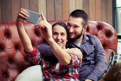 Couplez se reposer sur le sofa et prendre une photo de selfie Images libres de droits