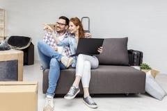 Couplez se reposer sur le sofa tandis qu'il café potable photos libres de droits