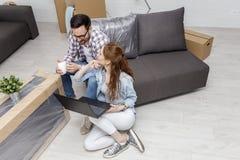 Couplez se reposer sur le sofa tandis qu'il café potable photographie stock libre de droits