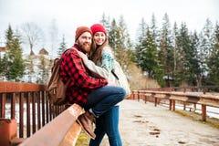 Couplez se reposer sur le vieux pont dans la forêt Image stock