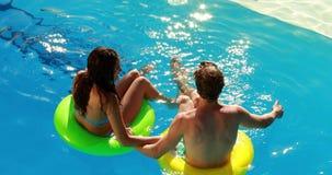 Couplez se reposer sur les anneaux gonflables dans la piscine banque de vidéos
