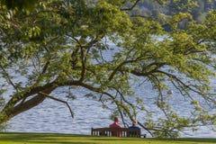 Couplez se reposer sur un banc regardant fixement le lac Windremere dans Ambleside Images stock
