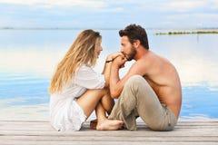 Couplez se reposer sur une jetée sous un ciel bleu à un coucher du soleil Image libre de droits