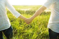 Couplez tenir des mains avec la vue romantique au champ ensoleillé Image libre de droits