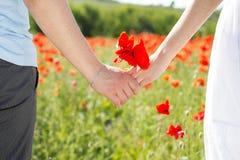 Couplez tenir des mains dans les domaines des pavots Photos libres de droits
