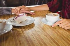 Couplez tenir des mains et avoir le café et le gâteau ensemble Image stock