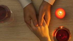 Couplez tenir des mains pendant le dîner romantique avec des bougies, jour de valentines de saint banque de vidéos