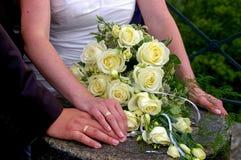 Couplez tenir des mains pendant le mariage avec des anneaux et des fleurs de mariage Images libres de droits