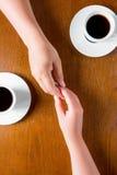 Couplez tenir des mains sur la table dans le café Photographie stock