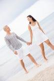 Couplez tenir des mains tout en marchant sur la plage Image stock