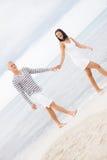 Couplez tenir des mains tout en marchant sur la plage Photographie stock