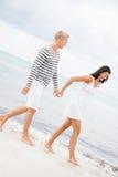 Couplez tenir des mains tout en marchant sur la plage Photos libres de droits