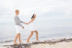 Couplez tenir des mains tout en marchant sur la plage Image libre de droits