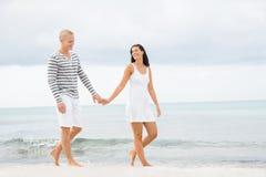 Couplez tenir des mains tout en marchant sur la plage Images stock