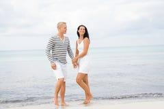 Couplez tenir des mains tout en marchant sur la plage Photo libre de droits