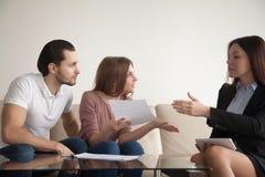 Couplez tenir des papiers discutant avec l'agent ou le banquier au sujet de la fraude photos libres de droits