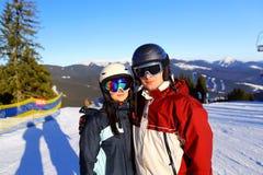 Couplez tenir des skis se tenant sur le dessus de montagne ensemble Foyer sélectif photo stock