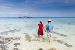 Couplez tenir la main marchant dedans à la mer clair comme de l'eau de roche avec long merci Photographie stock