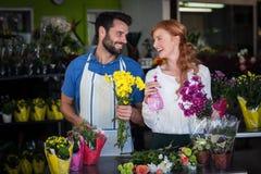 Couplez tenir le groupe de fleurs et de bouteille de jet Photo stock