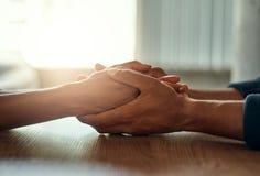 Couplez tenir leurs mains sur le bureau photographie stock