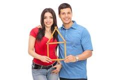 Couplez tenir un ruban métrique sous la forme de maison Photos libres de droits