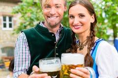 Couplez Tracht de port posant avec des verres dans le jardin de bière Photographie stock