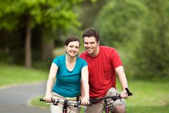 Couply Smiling on Bicycyles - horizontal Royalty Free Stock Photos