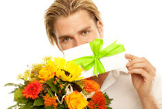 Coupon. Blond man holding a coupon in front of his face Stock Images