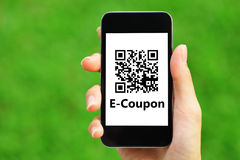 Coupon QR code on smart phone. Hold by hand Stock Images