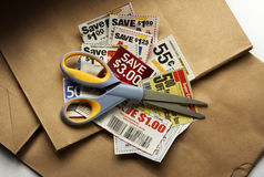 Coupon savings. Savings coupons and scissors shot on shopping bags with soft drop shadow royalty free stock photos