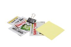 Coupons In A Black Clip. Assorted money saving grocery coupons held together with a black binder clip and topped with a blank sticky note for copy space Stock Image