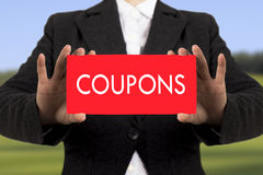 Coupons. Businesswoman in a black jacket shows a card with the inscription coupons. Selective focus Stock Photo
