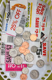 COUPONS AND COINS. SOME COINS AND COUPONS ON A SMALL BASKET Stock Photos