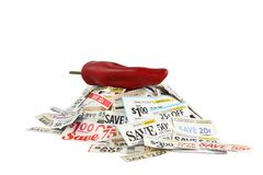 Coupons With Red Hot Pepper. Coupons in a pile topped with a red hot pepper. Hot savings concept Royalty Free Stock Image