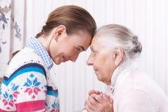 Coups de main, aîné de concept de soin aux personnes âgées et travailleur social tenant des mains à la maison Images libres de droits