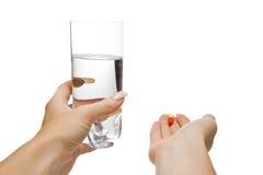 Coups de main avec l'eau et des pillules, d'isolement Photographie stock libre de droits