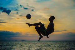 Coups de pied d'une boule Silhouette d'un homme sur une plage image stock