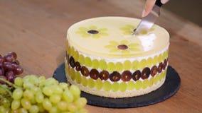 Coupure avec un g?teau de mousse de couteau avec des raisins G?teau rond de mousse d?cor? des raisins banque de vidéos