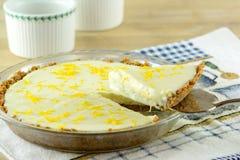 Coupure d'un morceau de dessert de gâteau au fromage de citron Images stock