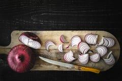 Coupure de l'oignon rouge sur la vue supérieure de conseil en bois images libres de droits