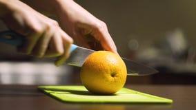 Coupure de l'orange dans le demi ‹découpé en tranches d'†de ‹d'†sur un conseil vert clair banque de vidéos