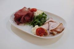 Coupure de la viande et du jambon d'un plat blanc et de quelques verts Photographie de nourriture photographie stock libre de droits