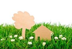 Coupure de papier de maison et d'arbre sur l'herbe. Photo libre de droits