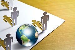Coupure de papier des gens restant avec le globe. Image libre de droits