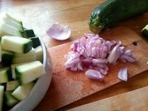 Coupure de quelques oignons et courgettes pour un dîner sain et délicieux photos stock