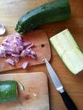 Coupure de quelques oignons et courgettes pour un dîner sain et délicieux images libres de droits