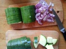 Coupure de quelques oignons et courgettes pour un dîner sain et délicieux images stock