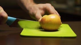 Coupure des moitiés d'une pomme dans le demi ‹découpé en tranches d'†de ‹d'†sur un conseil vert clair banque de vidéos