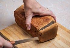 Coupure du pain brun Photos stock